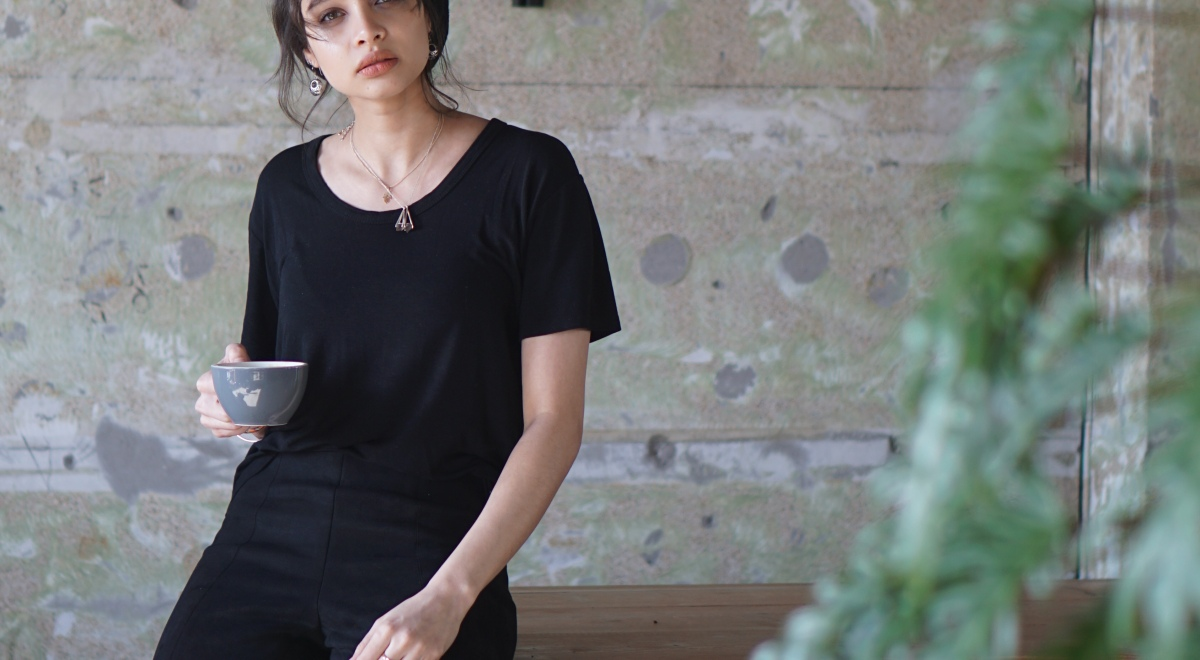 woman_wearing_black_tshirt_and_trousers_sitting_on_table_with_coffee_in_hand