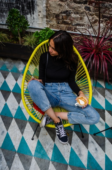 girl_sitting_on_yellow_chair_wearing_non_stretch_denim_and_black_high_neck_having_coffee