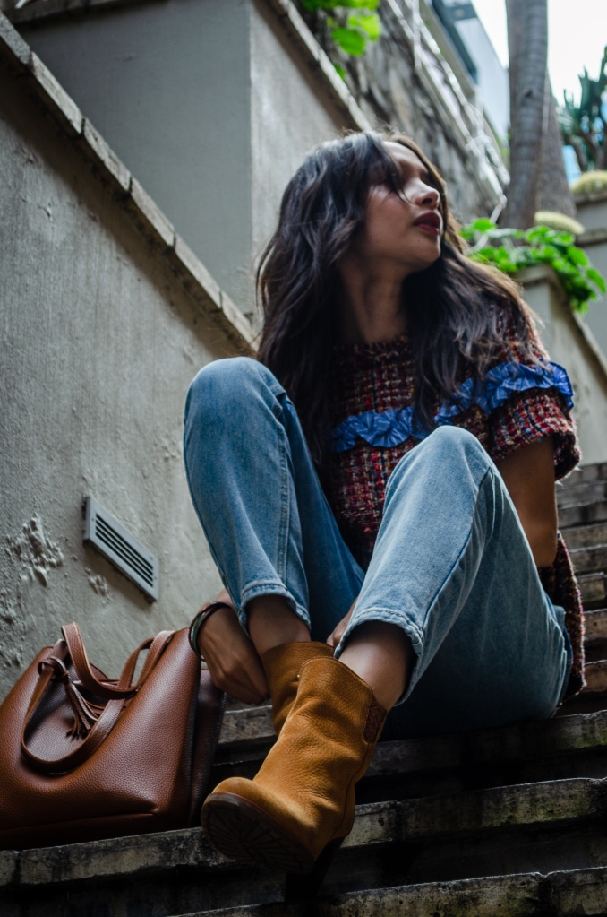 woman_on_steps_wearing_brown_boots_blue_jeans_and_pink_top
