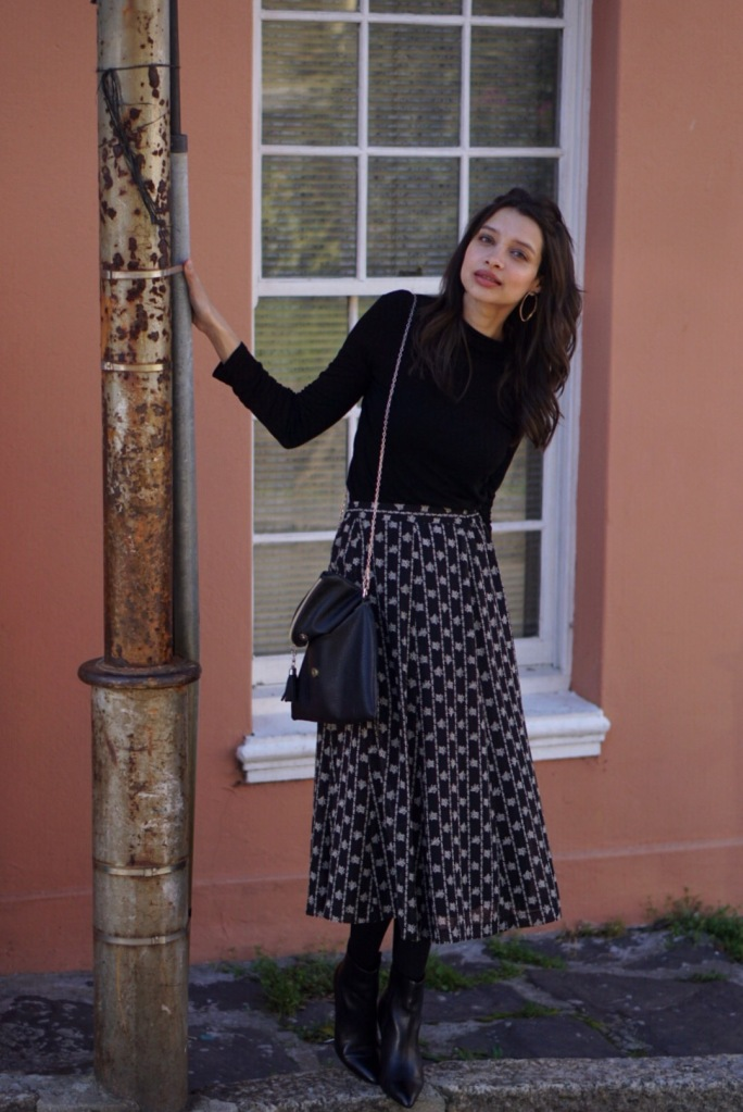brunette_woman_on_street_wearing_vinatge_skirt_boots_and_black_highneck