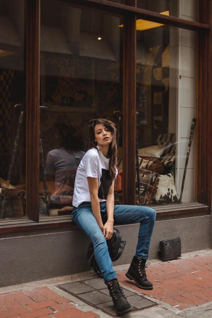 female_brunette_wearing_jeans_boots_calvin_klein_tshirt